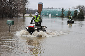 Person drivingn an ATV through flood waters.